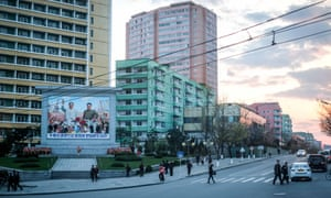 Elaborate flower arrangements are lined up in tribute below a mural of Kim Il-sung and his son Kim Jong-il. The vast image looms over an intersection in central Pyongyang, North Korea.