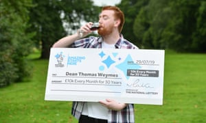 Dean Weymes celebrates with a large cheque and a suspiciously dark-hued drink.