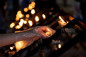 Wearing gloves for protection, a Christian lights a candle at a church in Metro Manila, the Philippines