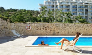 Two women in swimming costumes at the outdoor pool of Inhawi Boutique Hostel, Malta.