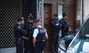 Police guard a residential building in Sabadell, north of Barcelona, after the nine arrests.