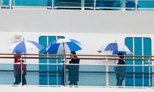 Passengers wearing masks walk on a deck of the Diamond Princess cruise ship docked in Yokohama.