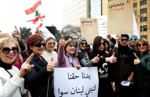 Women outside the government palace in Beirut hold a banner reading in Arabic: 'We demand our rights to build Lebanon together.'