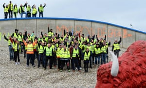 """Protesters stand next to a mock bison (a reference to the """"smart bison"""" emblem of road safety) on a roundabout on which is written """"Macron resign"""" as they block access to the A11 and A28 highways in St-Saturnin, near Le Mans, north-western France"""