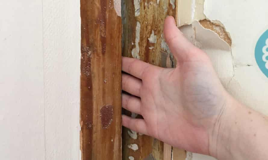 A resident can fit a hand in crack between flats.