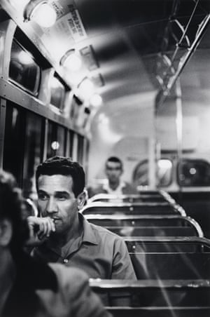 Charles Perkins sitting on a 60s bus underneath a row of lights