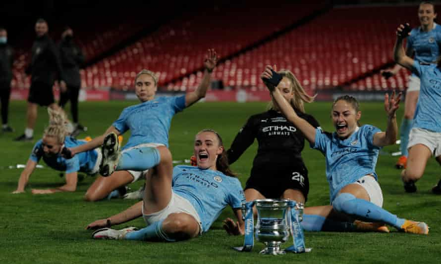 Man City players, including goalscorers Georgia Stanway (front left) and Janine Beckie (front right), celebrate with the trophy.