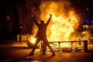 A protester poses in front of a burning barricade in Barcelona last week