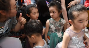 A parent advises her daughter as she waits to take the stage at a child model contest