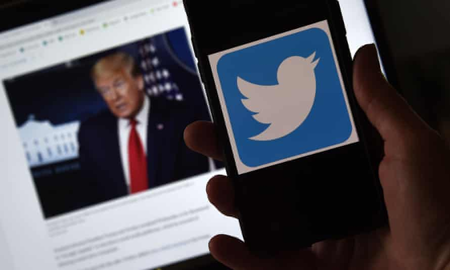Photo illustration of a Twitter logo displayed on a mobile phone with a President Trump's picture shown in the background
