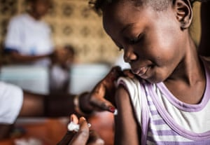 Yungi, aged 8, is among the first to receive her vaccination at one of the hundreds of vaccination stations set up across Kinshasa