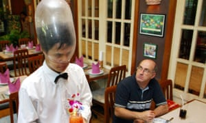 A waiter wears a condom on his head at the Cabbages and Condoms restaurant.