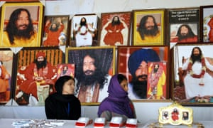 Indian followers of deceased guru Ashutosh Maharaj sit in front of posters bearing his image at a stall during a congregation at his ashram.