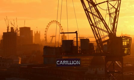 The sun sets behind a construction crane showing the branding of British construction company Carillion photographed on a building site in central London