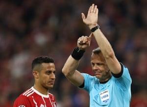 The referee signals handball.