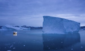 A boat navigates around icebergs in eastern Greenland.