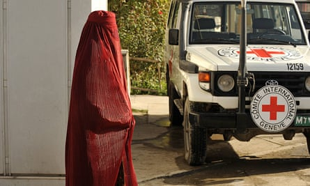 An Afghan woman walks past a vehicle at the International Committee of the Red Cross office in Kabul