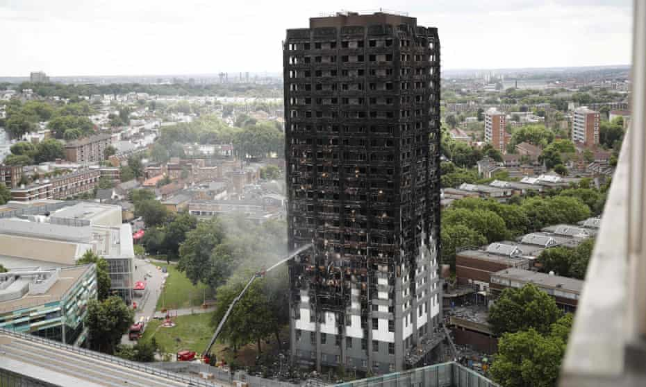 An automated hose sprays water onto Grenfell Tower.