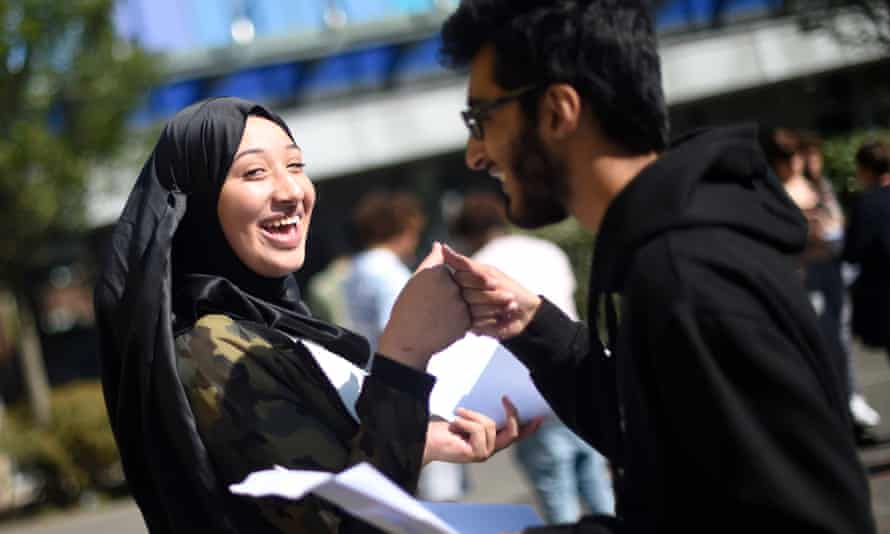 Two students do a celebratory fist bump after getting their results in London.