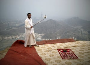 A pilgrim uses a selfie stick to take pictures on top of Mount Thawr