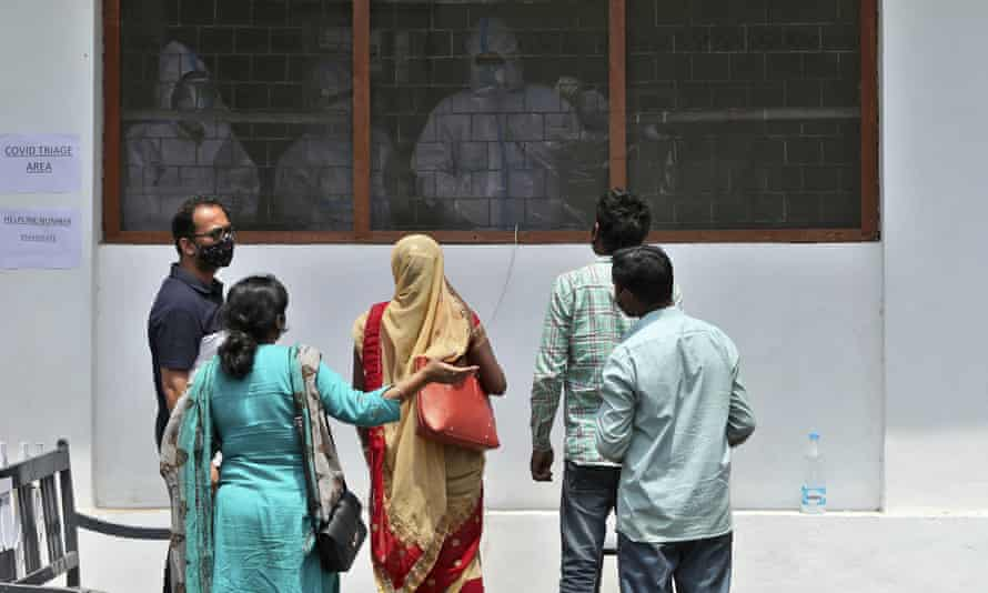 Paramedics in PPE suits and Covid-19 patients and their relatives at a government-run hospital in Jammu, India, 7 May 2021.