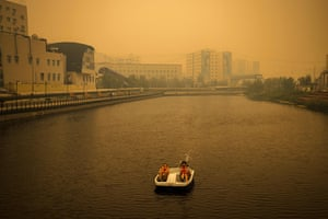 A couple ride a pedal boat as smoke from nearby forest fires hangs over the city of Yakutsk