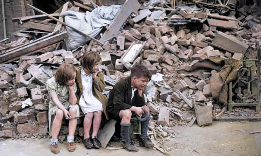 Three children sit by the rubble that had been their home after an overnight German bombardment destroyed the building in East London.
