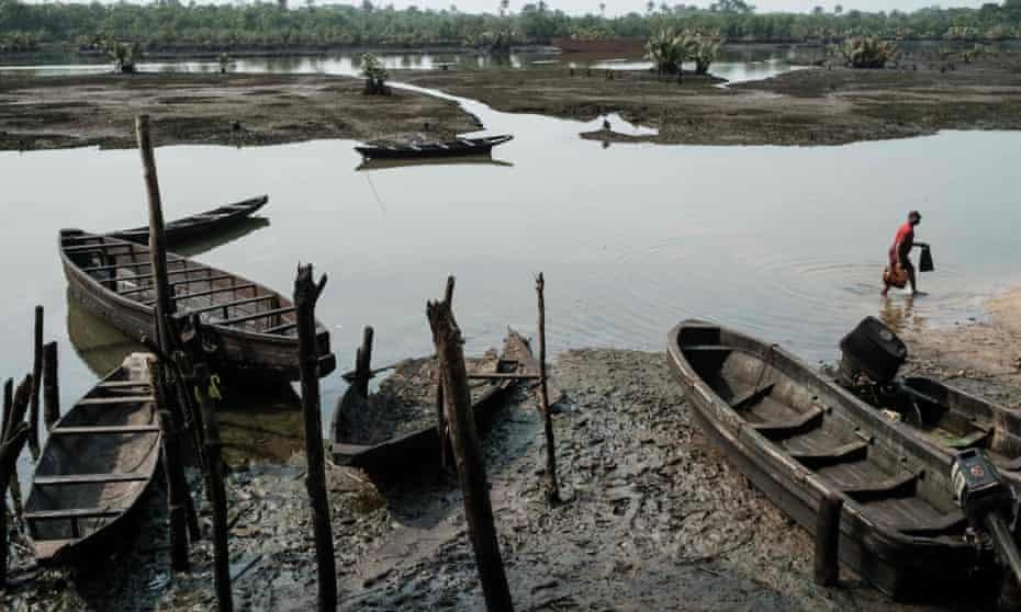 A man walks past oil-smeared fishing boats near Bodo in the Niger delta region in February 2019.