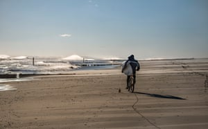 Cycling along the shore with board at Rockaway