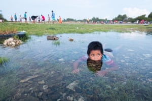 A boy swims in a flooded area of Funafati, Tuvalu
