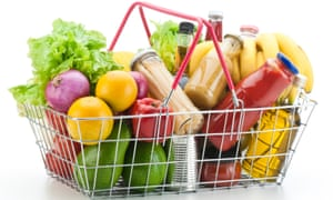 Wire shopping basket filled with groceries and vegetables
