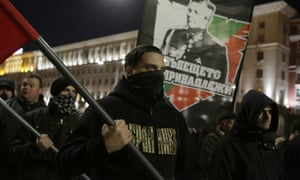 Bulgarian nationalists march in Sofia holding flags and a portrait of Gen Lukov