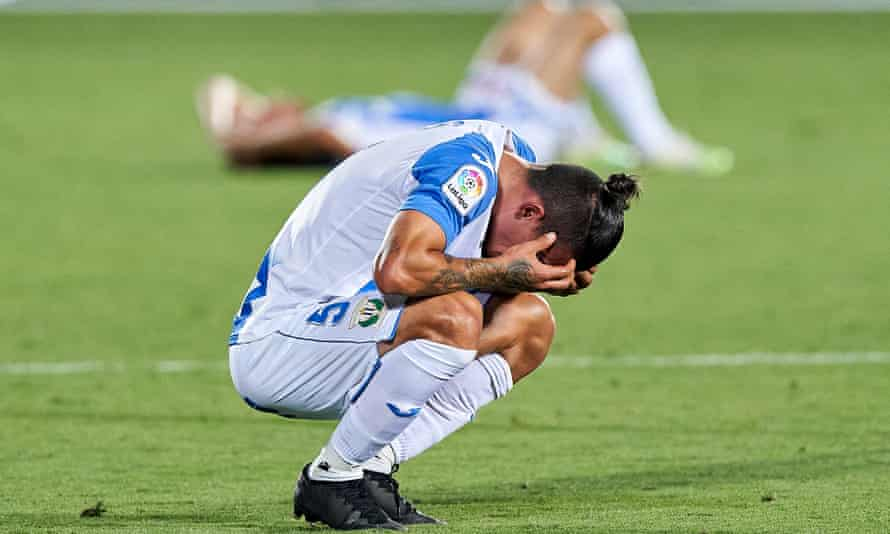 Leganés players crumple on the pitch after their relegation.