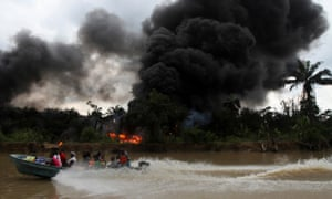 A passenger speedboat churns up the water, as an oil refinery is left burning in Bayelsa, Nigeria