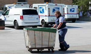 A United States Postal Service (USPS) worker pushes a mail bin outside a post office in Royal Oak, Michigan, this summer.