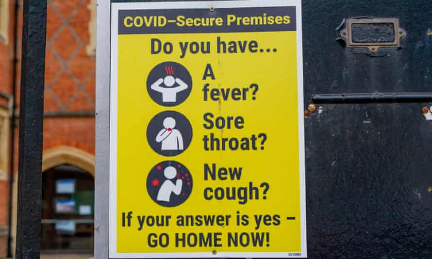 A 'Covid-secure premises' sign outside a building urging people to go home if they have symptoms.