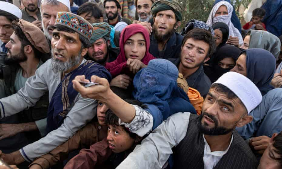 Displaced Afghans who have fled the advancing Taliban reach out for aid at a camp in Kabul, Afghanistan