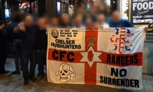 A Chelsea Headhunters flag featuring an SS Totenkopf symbol, held up outside a bar in Budapest