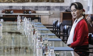 Aung San Suu Kyi at a table surrounded by empty chairs