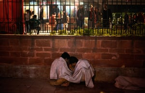 People smoke heroin on the sidewalks in New Delhi, India.
