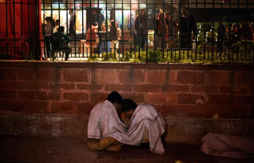 People smoke heroin on the sidewalks in New Delhi, India.