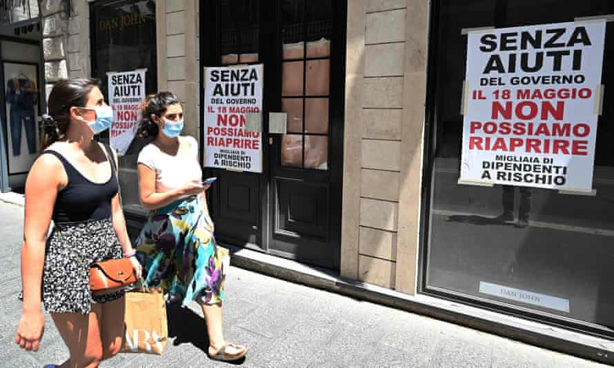 Women walk past a closed men's clothing shop, on which signs read 'Without government aid we can not reopen' in Rome