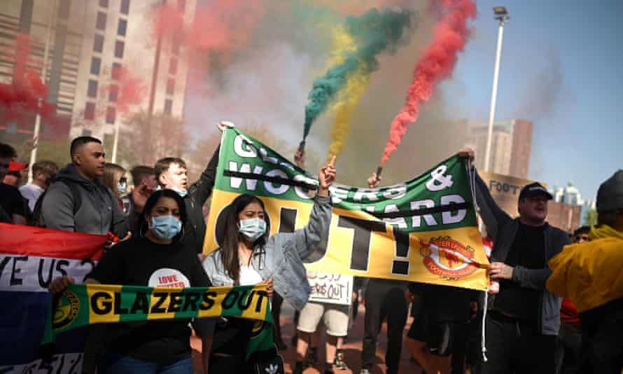 A group of fans in face masks holding up banners demanding a change of ownership and discharging multicoloured smoke generators in red, green and yellow