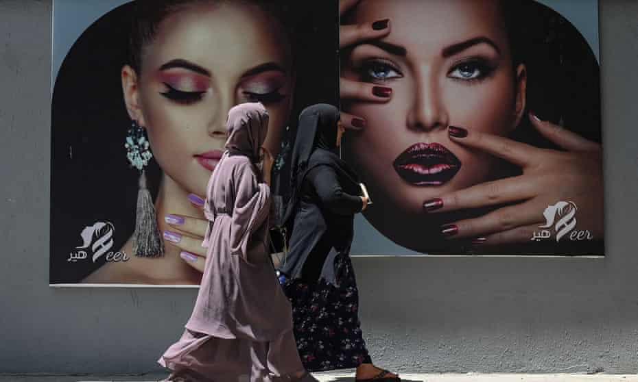 Women walk past a beauty parlour billboard in Kabul last week.
