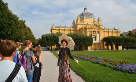 A costumed guide, in front of a grand civic building,  on one of Secret Zagreb's tours