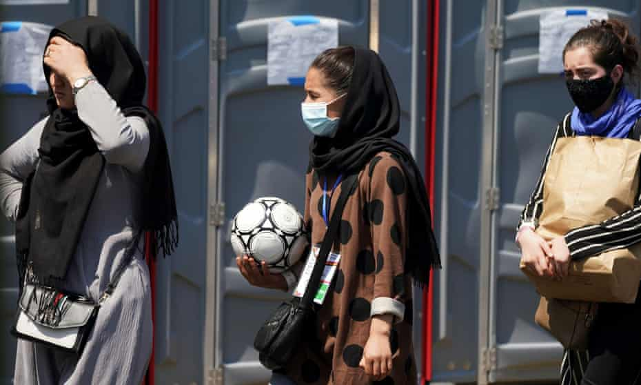 A woman holding a football and wearing a CAFA (Central Asian FA) lanyard waits in line at a refugee processing centre near Dulles airport, Washington DC.