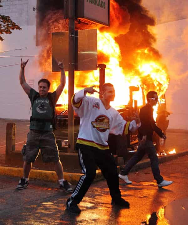 Canucj fans pose in front of a burning vehicle during the Vancouver riots in 2011.