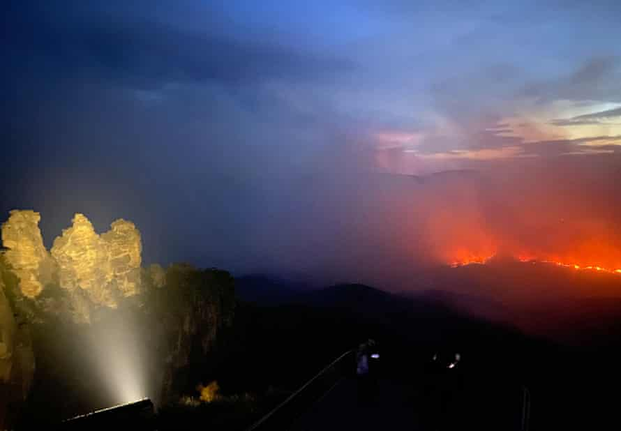 A bushfire rages in the Blue Mountains as the Three Sisters is floodlit in the foreground. More than 800,000 hectares of forest in NSW national parks have burned in unprecedented fires since 1 July.