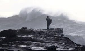 A surfer watches turbulent seas at Avoca Beach in Sydney, Australia