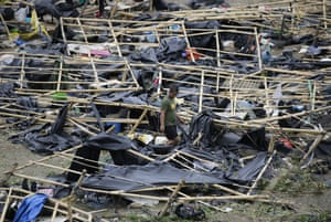 A policeman walks through collapsed makeshift tent shelters in Tuguegarao, Philippines